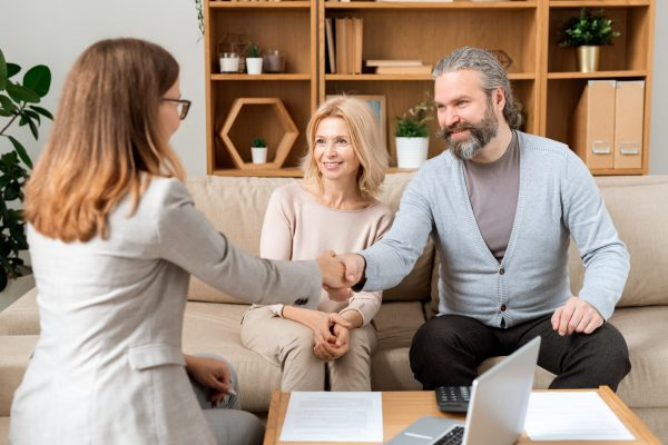 Happy mature bearded man giving hand to young real estate advisor